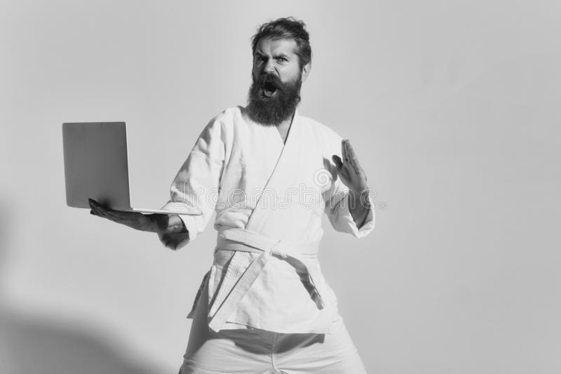 Bearded angry karate man in kimono with laptop royalty free stock photography