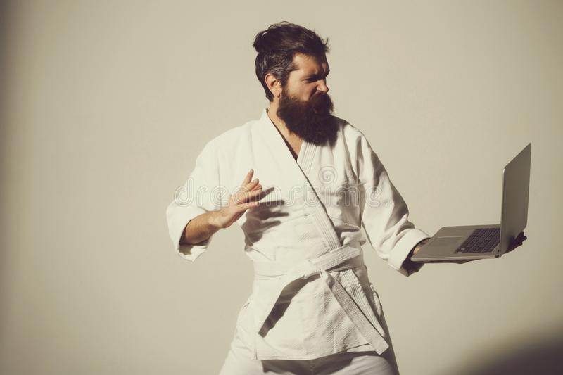 Bearded angry karate man in kimono with laptop. Bearded karate man, long beard, brutal caucasian hipster with moustache in white kimono holds laptop with angry stock photo