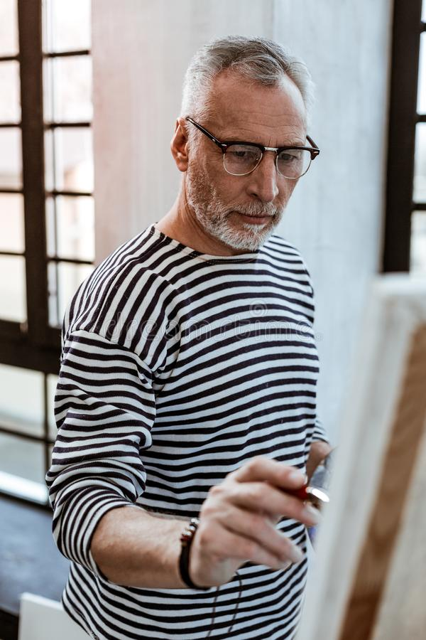 Bearded artist wearing glasses standing near canvas and painting stock photo
