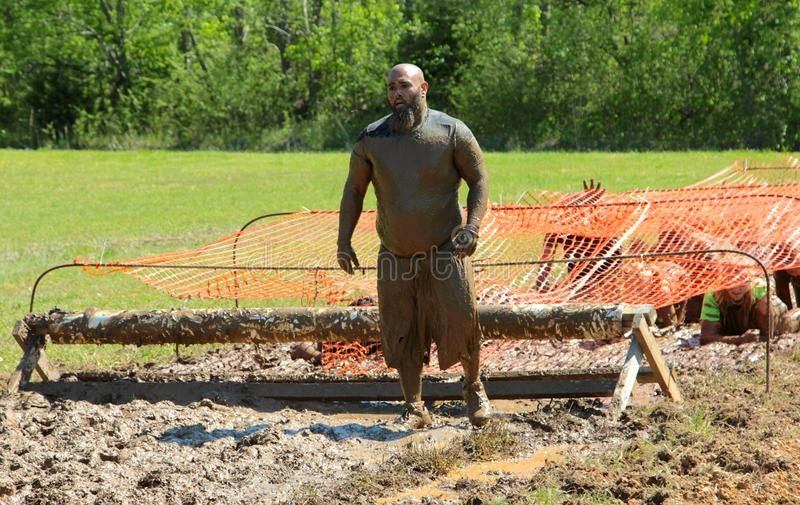 Bearded Asian Man Stares Down Obstacle Course during Annual Mud Run. Bearded Asian man stares down muddy obstacle course while competing in Naval Station royalty free stock photography