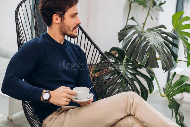Bearded attractive man is having a drink stock images