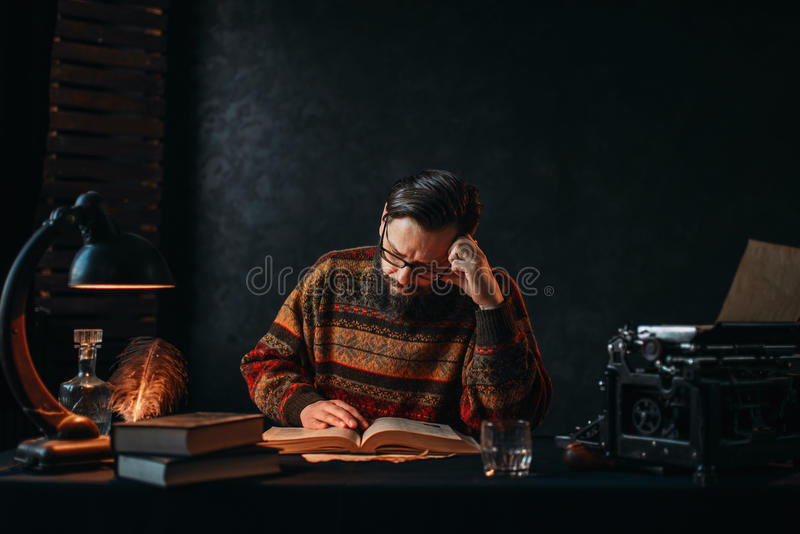 Bearded author in glasses reading a book. Retro typewriter, feather, crystal decanter, books and vintage lamp on the desk royalty free stock photo