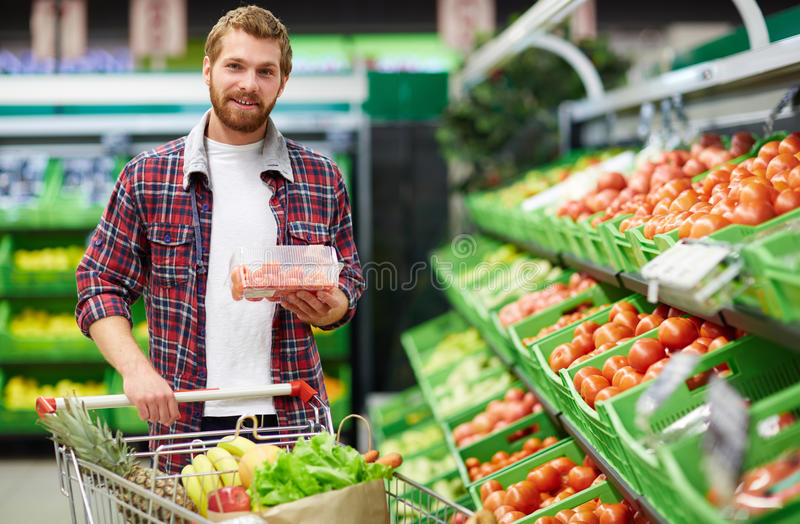 Bearded bachelor shopping in hypermarket. Young bearded bachelor holding packaging box with cherry tomatoes and looking at camera while shopping in fruit and stock photos