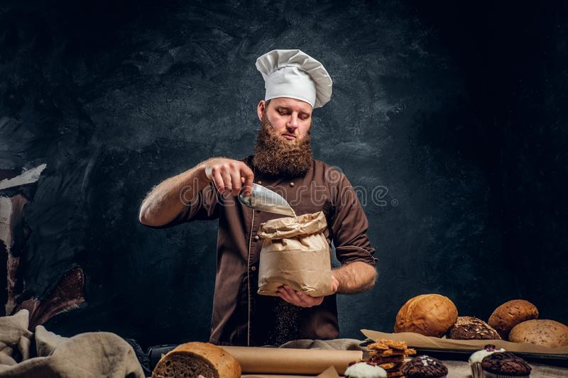 A bearded baker wearing a cook uniform sprinkling some flour in bag, standing next to a table, decorated with delicious royalty free stock photography