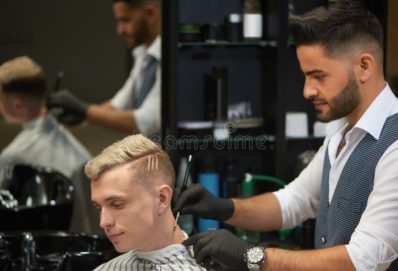 Bearded barber shaving neck of client using razor. stock photos
