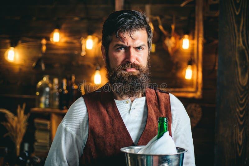 Bearded bartender or waiter in work uniform. Long bearded waiter or servant. Brutal bearded servant. Restaurant staff royalty free stock photos