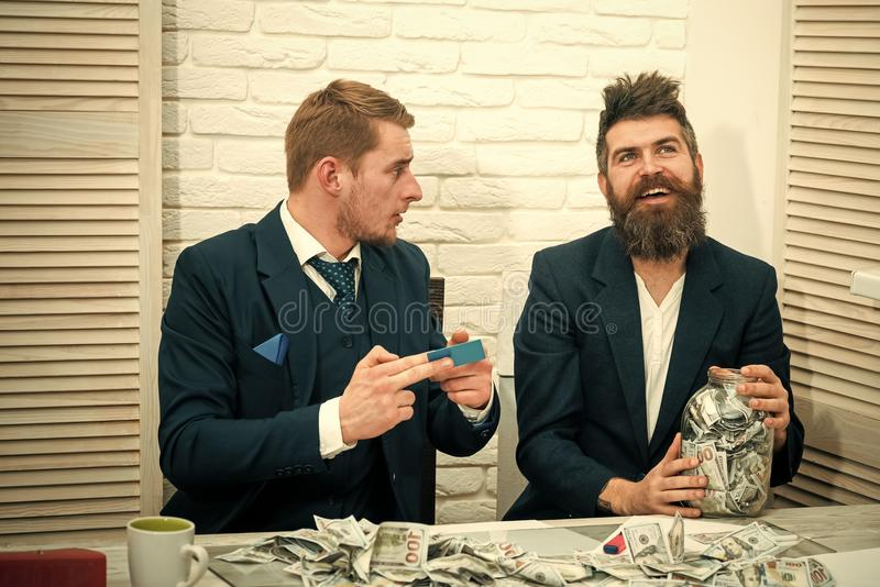 Bearded boss holds jar full of cash, colleague holds credit card. Business profit, keeping money in jar or bank account. Cash and banking concept. Business royalty free stock photo