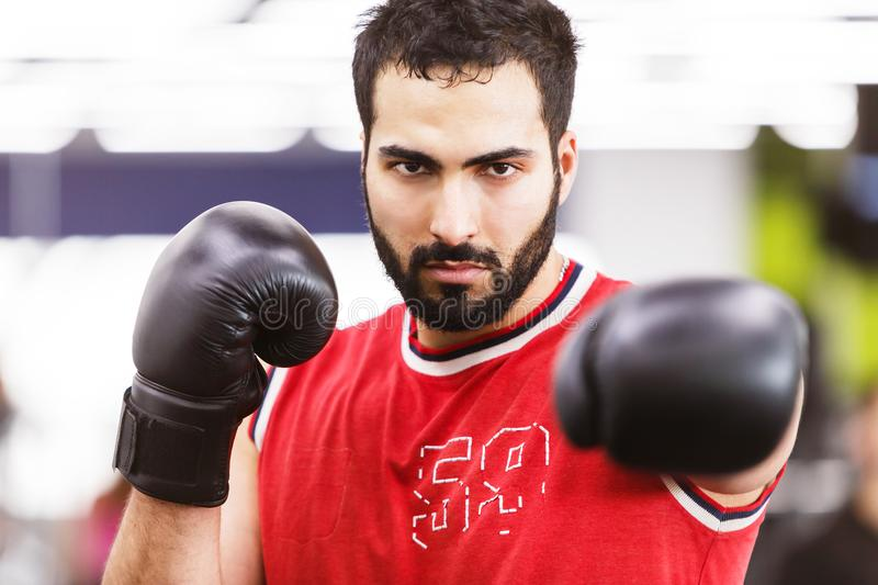 The Boxing Man. Bearded boxing man wears red shirt and black gloves in the ring royalty free stock photography