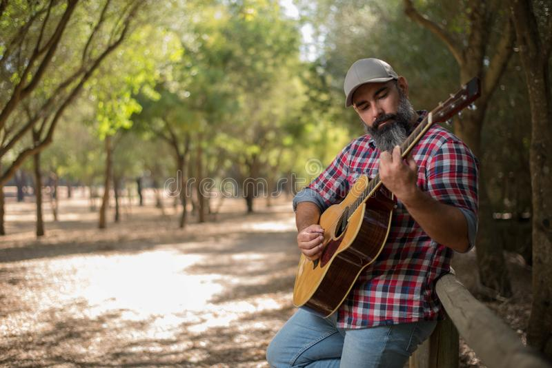Bearded boy with a guitar in the forest. Bearded boy whith a cap playing guitar in the forest under the trees royalty free stock photo