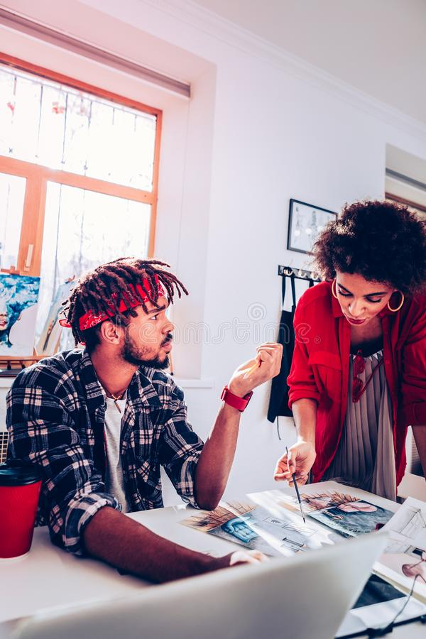 Bearded boyfriend with dreadlocks looking at his woman. Bearded boyfriend. Bearded handsome stylish boyfriend with dreadlocks looking at his woman royalty free stock image