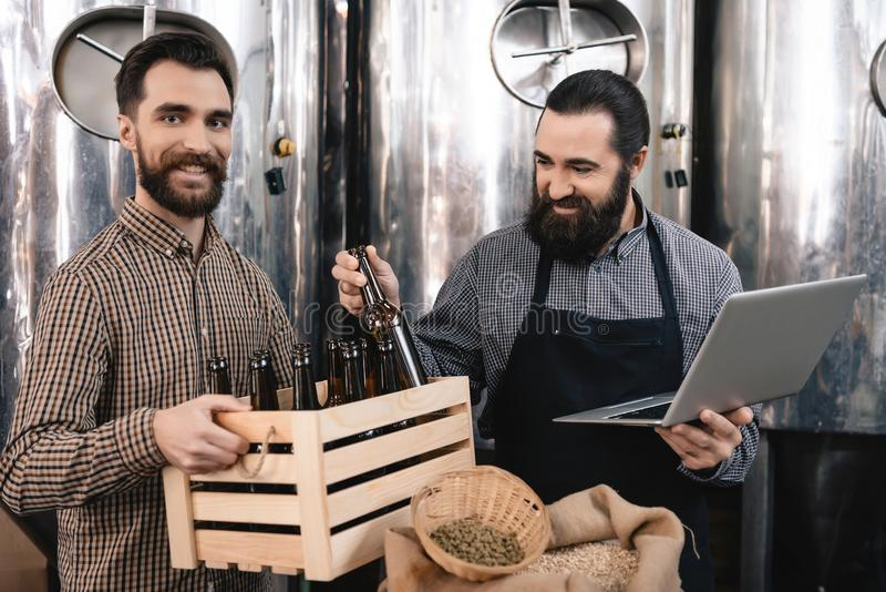 Bearded brewer in apron with laptop takes out bottle from box, which is held by cheerful man. Brewing. Brewery. Beer crafting. Process of beer manufacturing royalty free stock image