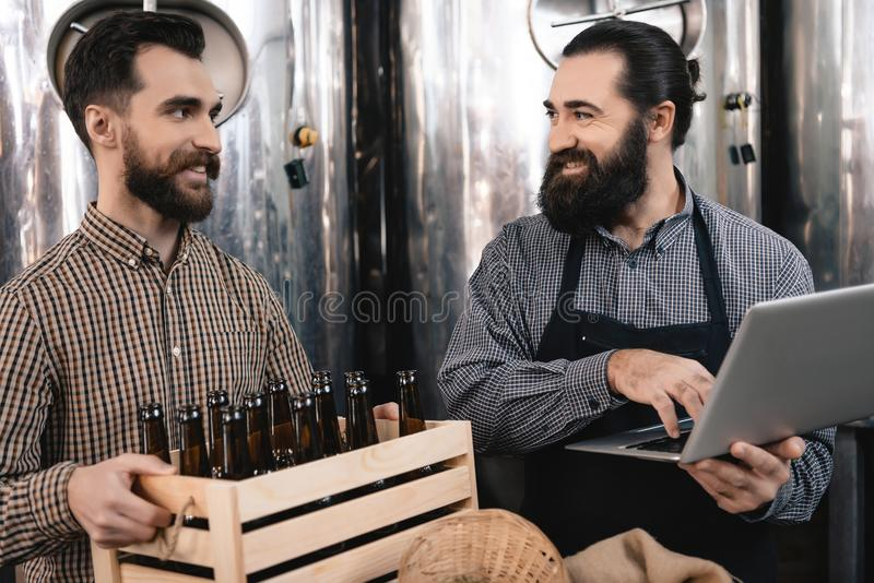 Bearded brewer in apron looks at merry man holding box of empty bottles. Bearded brewer in apron looks at merry men holding box of empty bottles. Brewing royalty free stock image