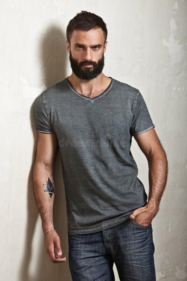 Bearded brutal man wearing grey t-shirt royalty free stock photo