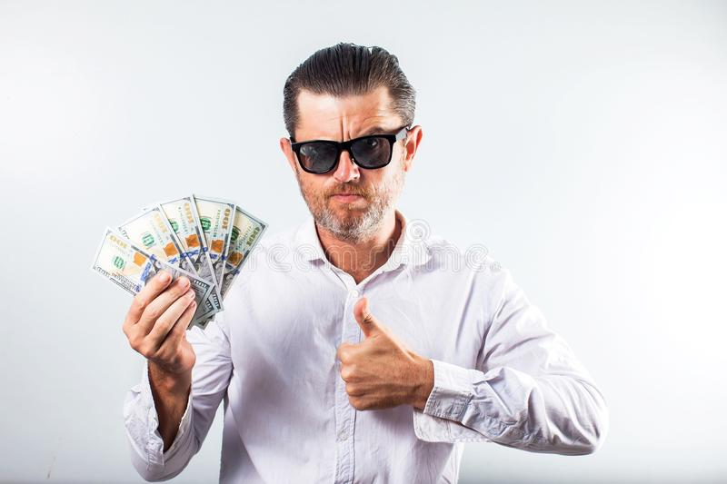 Bearded business man in shirt holding money and looking at the c royalty free stock image