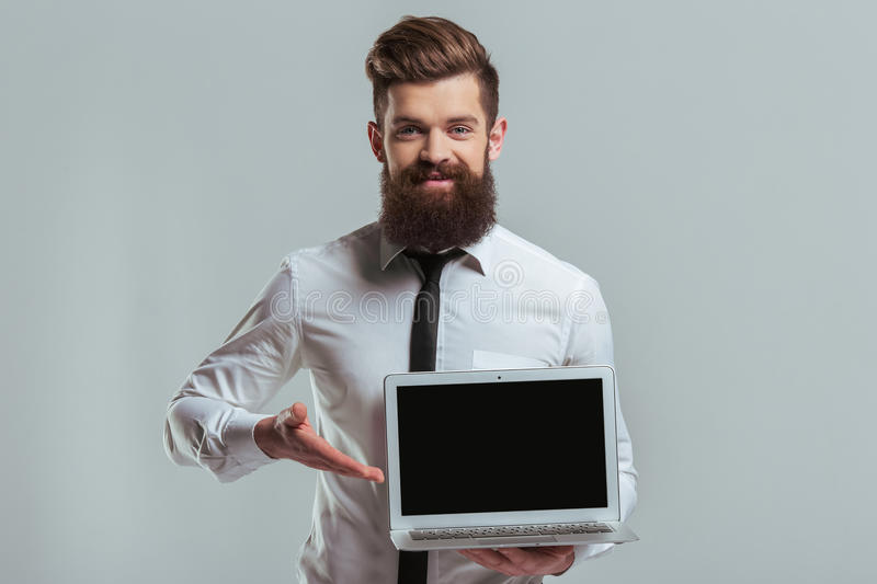 Bearded businessman with gadget. Handsome young bearded businessman in classic white shirt is showing a laptop and smiling, on a gray background stock photo