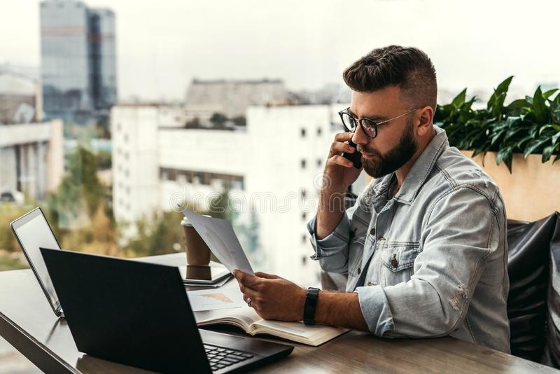 Bearded businessman hipster talking on phone while sitting at desk in office, sad looking at documents. Fall in profits. stock photography