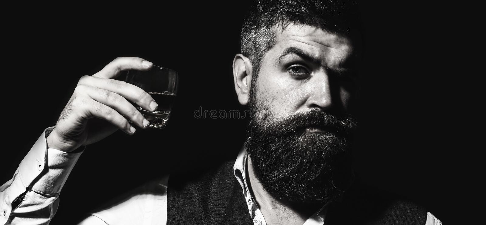 Bearded businessman in is holding a glass of whiskey. Handsome well-dressed man in jacket with glass of beverage. Adult stock image
