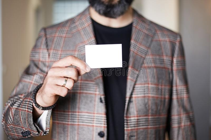 Bearded businessman holding hand empty white business card on blurred background. Mockup Copy Paste Blank Advertisement. royalty free stock image