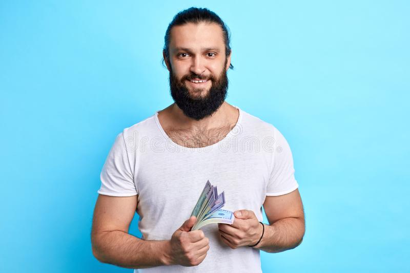 Bearded businessman with money looking at the camera stock photo