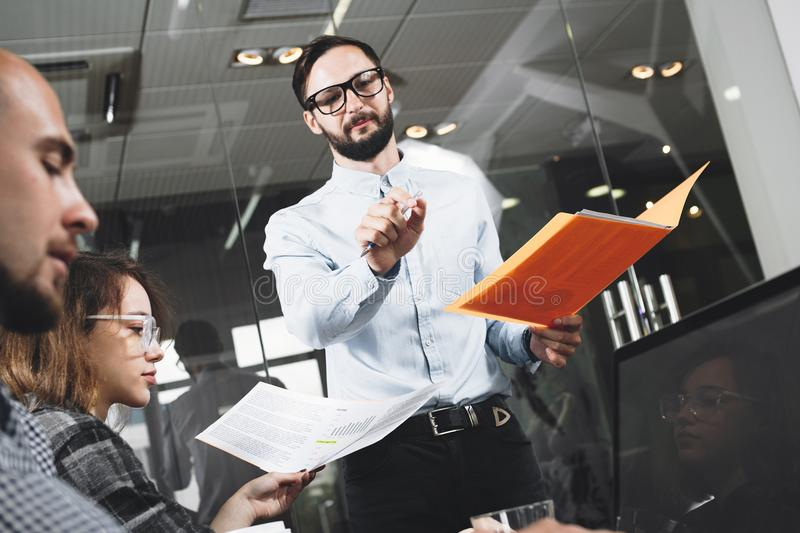 Bearded businessman presents a new project. HR manager conducts stock image