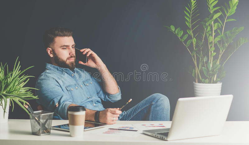 Bearded businessman sits in office at table,leaning back in chair and talking on cell phone while looking at laptop. Young bearded businessman sits in office at royalty free stock images