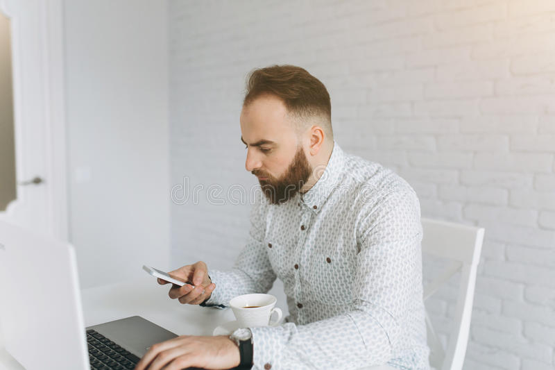 Bearded businessman sitting at a desk in the office. Handsome bearded businessman feels well and smiling. It sits in a bright office and thinking about work stock images