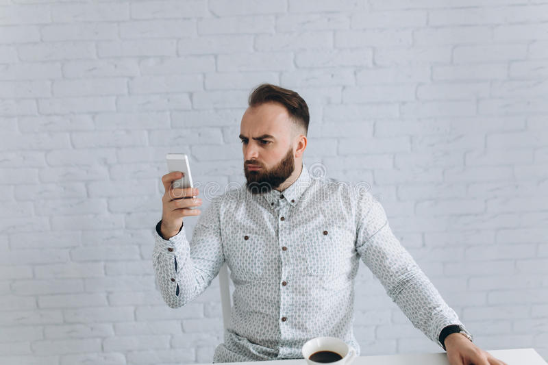 Bearded businessman sitting at a desk in the office. Handsome bearded businessman feels well and smiling. It sits in a bright office and thinking about work royalty free stock photo