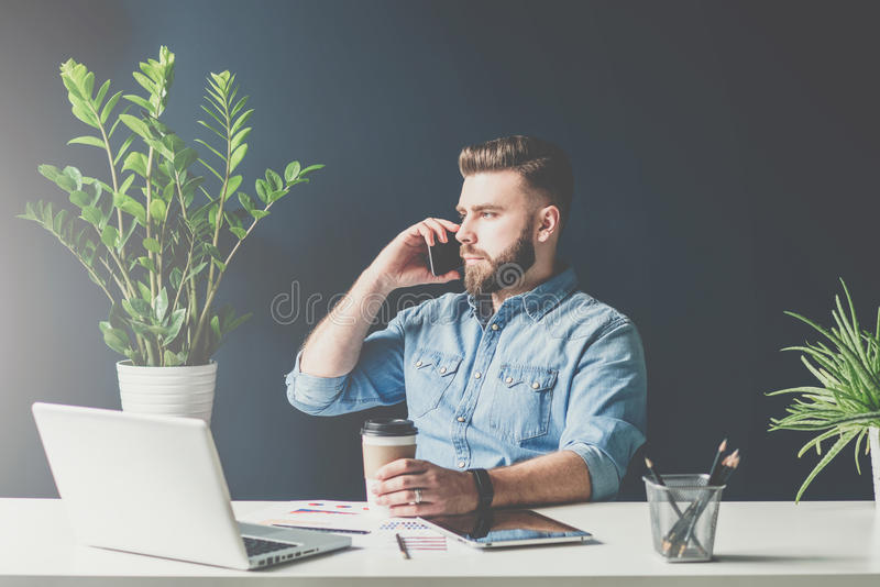 Bearded businessman is sitting in office at table and talking on cell phone while drinking coffee. royalty free stock image