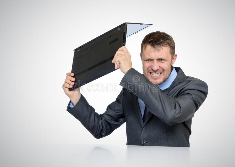 Bearded Businessman smashing his laptop stock image