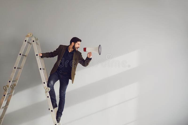 A bearded businessman on the stairs with a megaphone in hand shouts on a gray background. stock photography