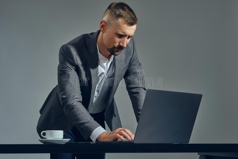 Bearded businessman with stylish mustache, dressed in a classic suit is working at laptop while standing at table in stock photo