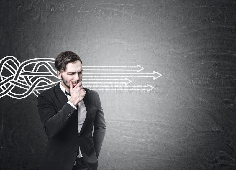 Download Bearded Businessman In A Suit Is Standing Near A Blackboard With Tangled Arrows Sketch Going Straight. Stock Image - Image: 83722033