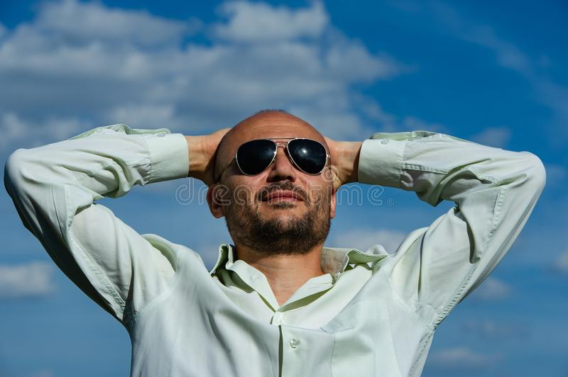 Bearded businessman with sunglasses folded his arms behind his h. Ead staring into the sky. Age 40 years stock images