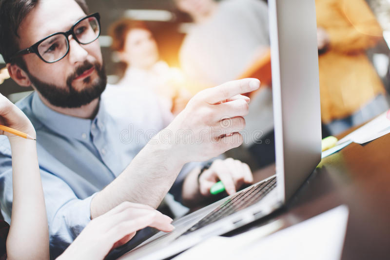 Bearded businessman tells a new startup plan to colleagues. Business idea discussing. Team working on a project in loft office. Blurred background stock images