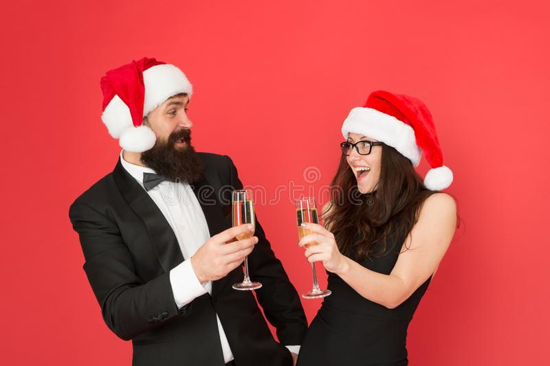 Bearded businessman in tuxedo and girl drinking sparkling wine red background. Winter party. Winter celebration. Merry royalty free stock photo