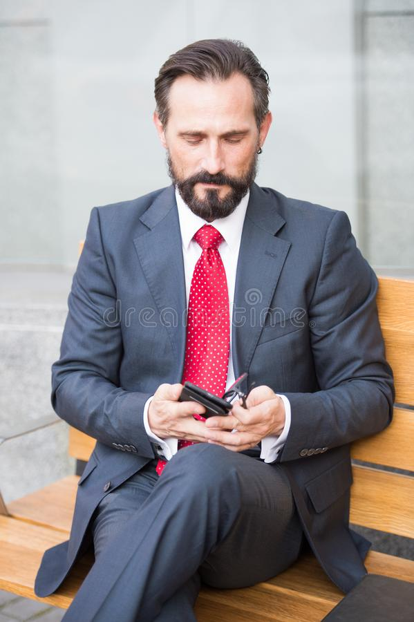 Bearded businessman using mobile phone while sitting on bench. Calm bearded handsome businessman wearing grey suit and sitting on wooden bench while using mobile stock photography