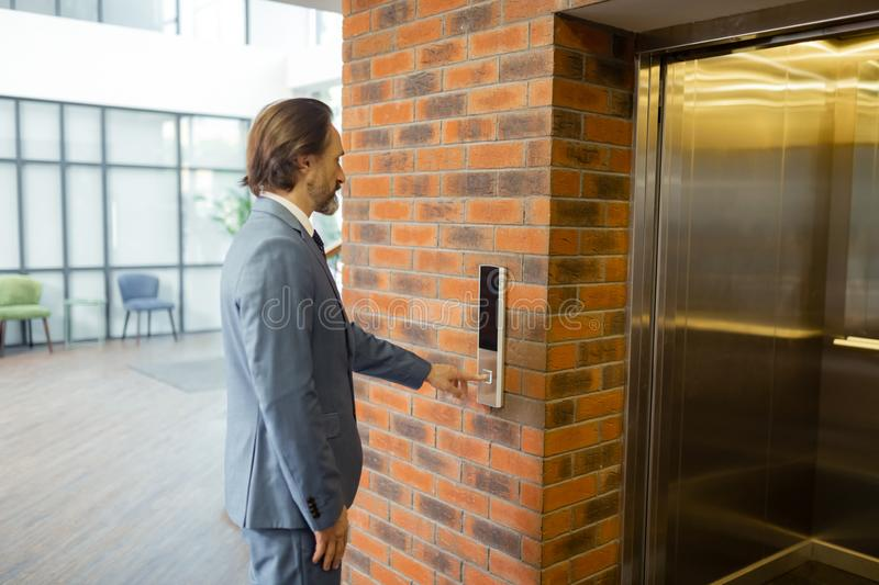 Bearded businessman waiting for elevator in the business center stock photos