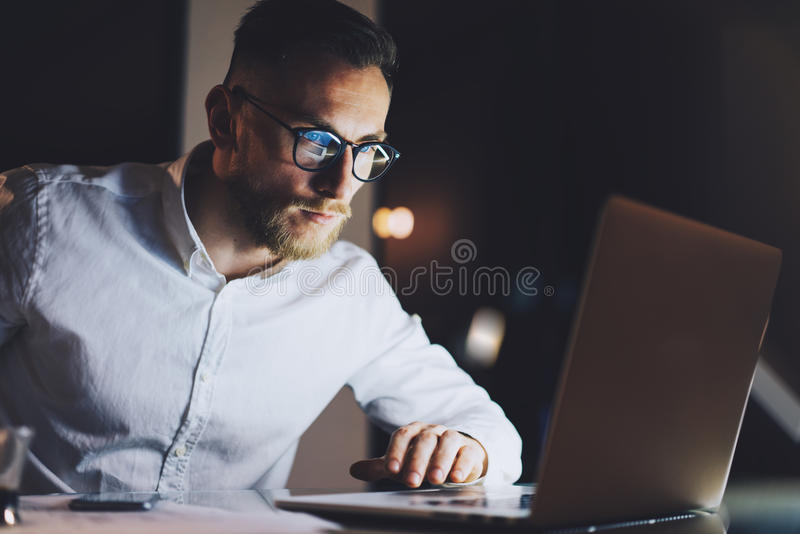 Bearded businessman wearing white shirt, glasses working on modern loft office at night. Man using contemporary notebook royalty free stock photos