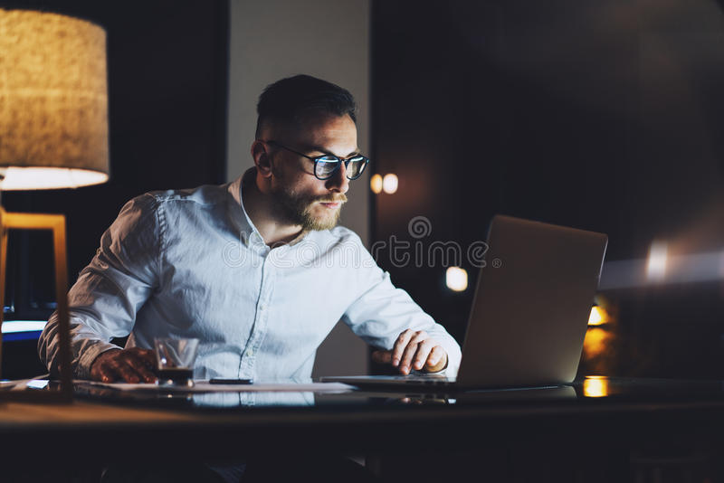 Bearded businessman wearing white shirt working on modern loft office at night. Man using contemporary notebook texting stock photography