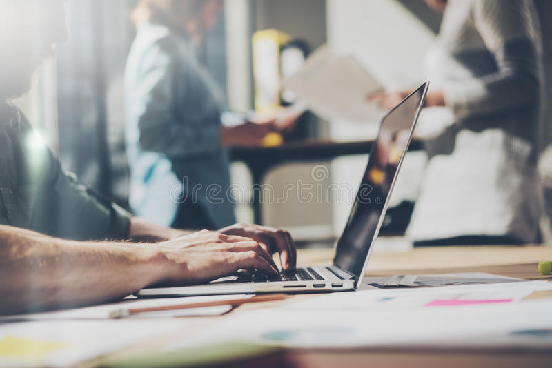 Bearded businessman working with team new project. Generic design notebook on wood table. Analyze plans hands, keyboard royalty free stock image