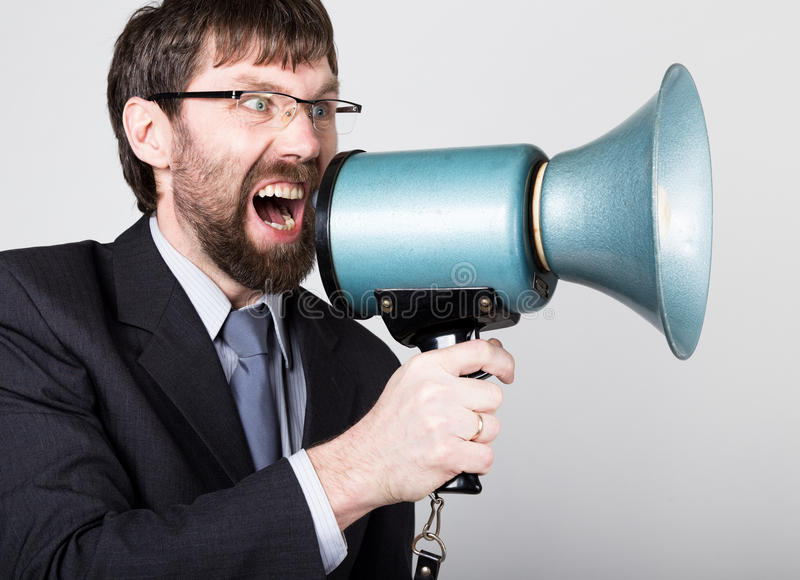 Bearded businessman yelling through bullhorn. Public Relations. man expresses various emotions. photos of young. Businessman wearing a suit and tie stock photos