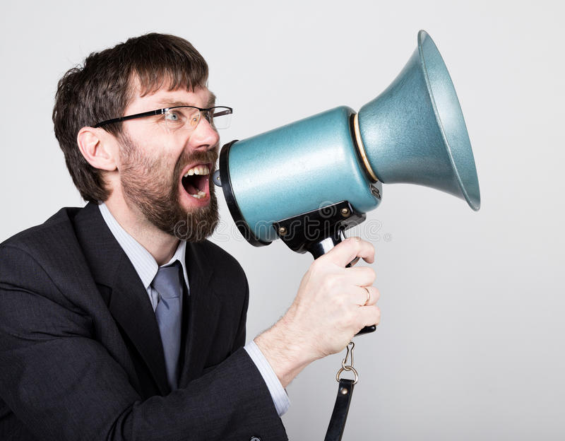 Bearded businessman yelling through bullhorn. Public Relations. man expresses various emotions. photos of young. Businessman wearing a suit and tie royalty free stock photos