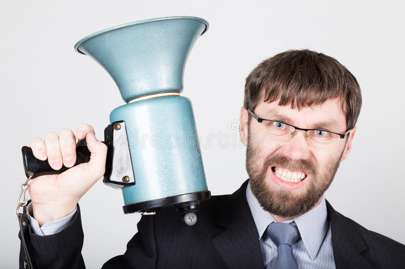 Bearded businessman yelling through bullhorn. Public Relations. man expresses various emotions. photos of young. Businessman wearing a suit and tie royalty free stock photography