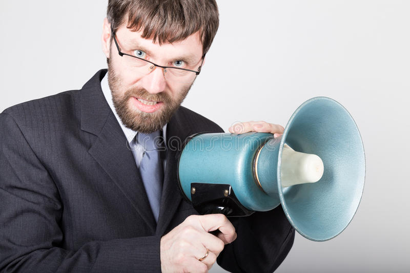 Bearded businessman yelling through bullhorn. Public Relations. man expresses various emotions. photos of young. Businessman wearing a suit and tie royalty free stock photo