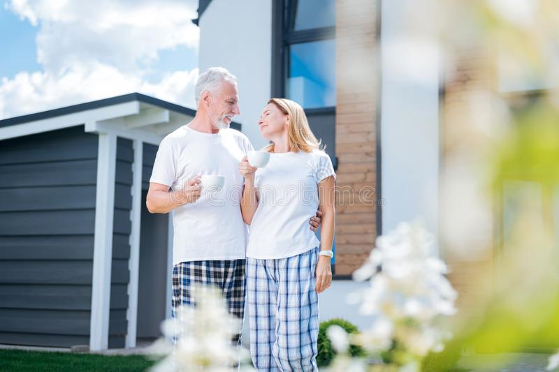 Bearded caring man hugging his happy wife drinking coffee in their courtyard stock photography