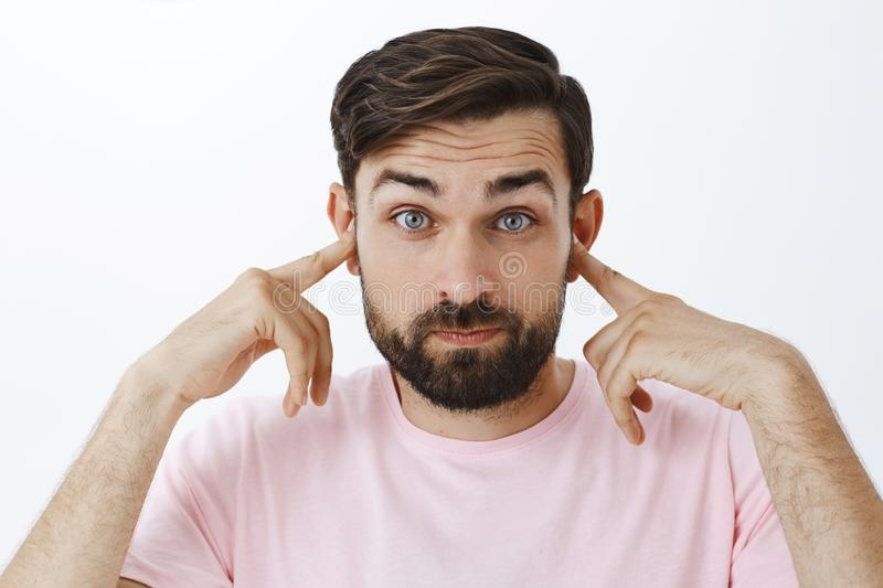 Bearded caucasian man close ears as standing in loud crowded place, holding index fingers in earholes pouting and stock photo