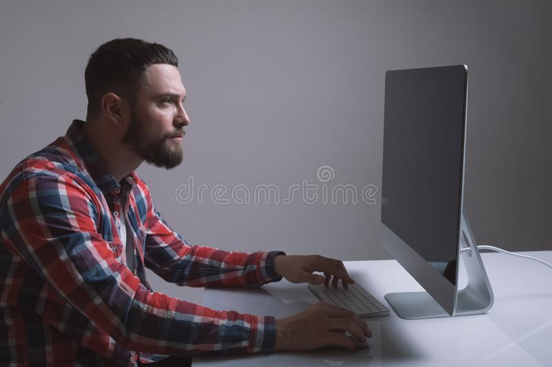 A bearded caucasian man is sitting behind the monitor of the computer. Muscular handsome guy is looking at the display during work royalty free stock image