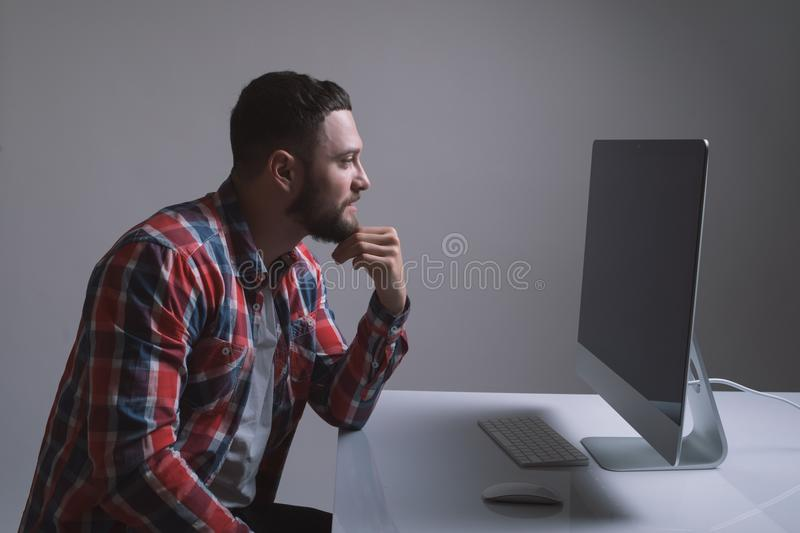 A bearded caucasian man is sitting behind the monitor of the computer. Muscular handsome guy is looking at the display during work stock photography