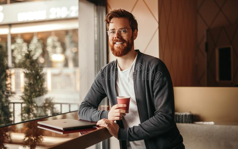 Bearded cheerful freelancer in cafe stock image