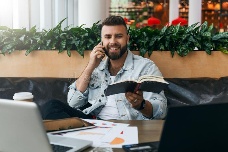 Bearded cheerful hipster man sits at table in front of laptops, talking on mobile phone while holding paper notebook. stock photography